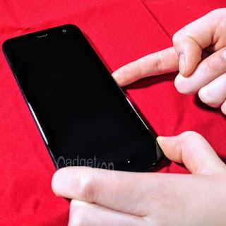 Kinderhand drückt Startknopf des HTC U11 Life; roter Hintergrund