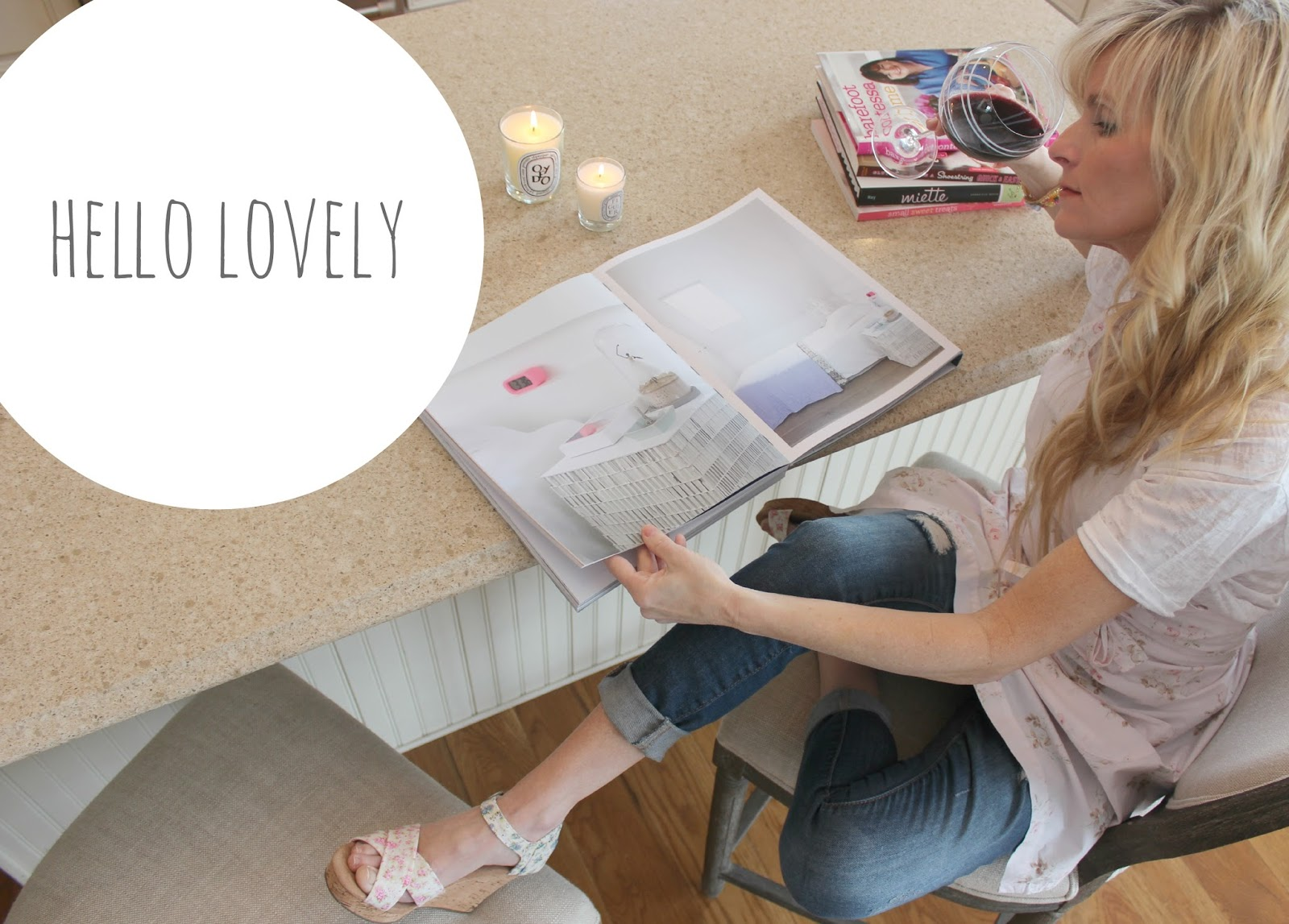 Michele with a design book at home and a glass of red - Hello Lovely.