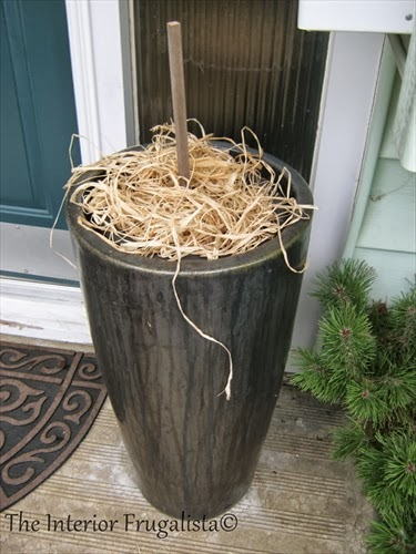 Fill large plant pot or urn with garden soil.  Stick garden stake into the center and cover soil with Raffia Ribbon.