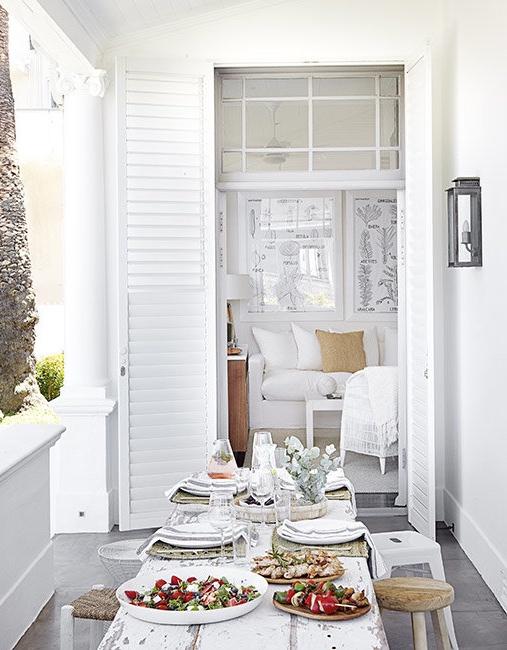 mesa de madera decapada en blanco en el porche chicanddeco