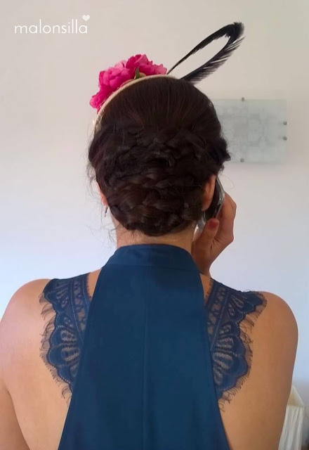 Invitada boda de espaldas con vestido azul petroleo de encaje y recogido con trenzas para tocado