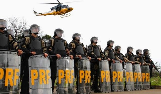 Grupo de agentes da Polícia Rodoviária Federal em formação portando escudos, cassetetes e capacetes acompanhados de um helicóptero sobrevoando uma operação em uma rodovia