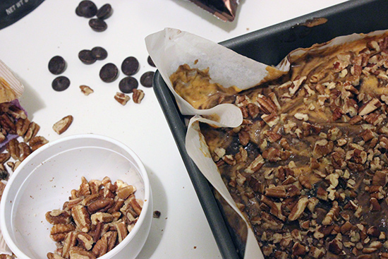 Topping Ghirardelli Chocolate Pumpkin Brownies with Chopped Pecans