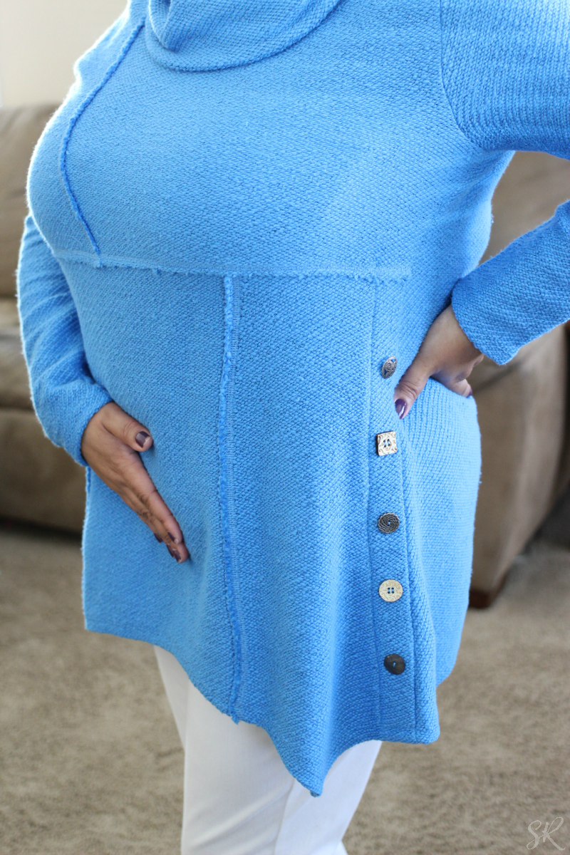 a woman showing button details on a blue sweater