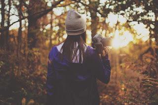 Une fille avec caméra dans la forêt