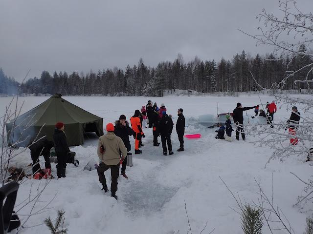 Ihmisiä jäällä avannon ympärillä, pystytettynä puolijoukkueteltta