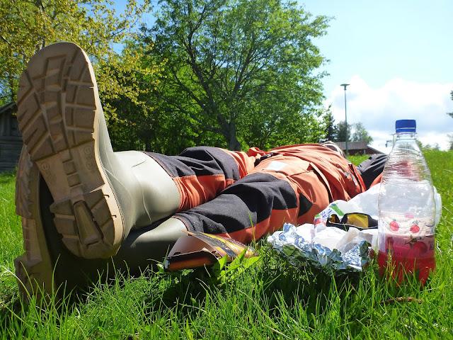 Pelastautumispukuinen henkilö makaa ruohikossa vieressään juomapullo ja aurinkolasit