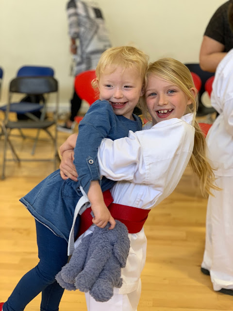 Big sister in Karate Gi and red belt picking her younger sister up and hugging her
