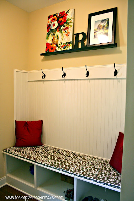 A mudroom with bead board, hooks a patterned seat cushion and two accent pillows