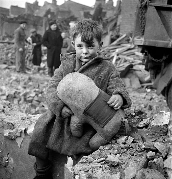 Abandoned boy holding a stuffed toy animal amid ruins following German aerial bombing of London, England, 1945