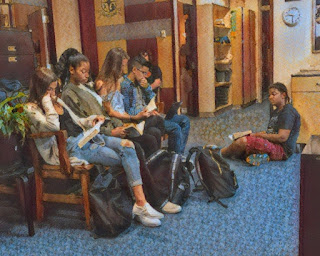 Four teenagers are sitting on a bench reading. Another is sitting on the floor also reading.