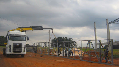 Caminhão guincho em preparativos para içar a tesoura metálica do frontão da obra, a ser fixada nos pilares de concreto armado, com encaixes projetados.