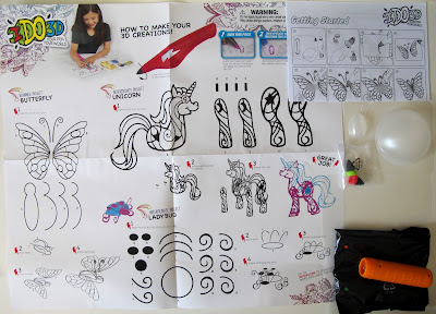 Contents of an I DO 3D pen set, including instruction and tracing sheets, plastic forms, pen tips, a spotlight and a bag with pens in it.