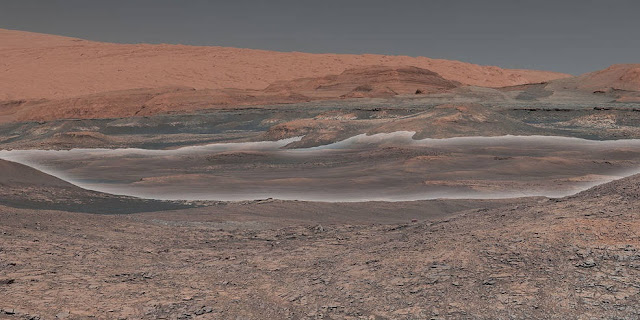 This mosaic taken by NASA's Mars Curiosity rover looks uphill at Mount Sharp, which Curiosity has been climbing since 2014. Highlighted in white is an area with clay-bearing rocks that scientists are eager to explore; it could shed additional light on the role of water in creating Mount Sharp. The mosaic was assembled from dozens of images taken by Curiosity's Mast Camera (Mastcam). It was taken on Sol 1931 back in January. Credits: NASA/JPL-Caltech/MSSS