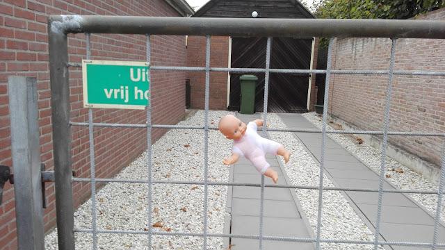Gewoon hek van een oprijlaan van een gewone burger met een babypop erin gehangen