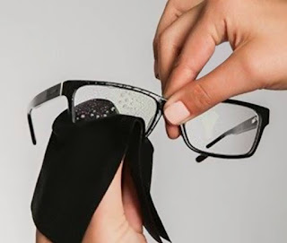 Image description: cleaning glasses while holding them from the bridge