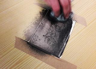 Um aluno movimenta de forma circular a tarlatana sobre a chapa da sua monotipia por forma a retirar o remanescente da tinta