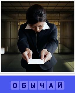 женщина наклонившись в протянутых руках подает бумагу