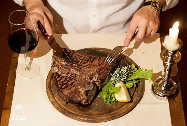 tavolo con calice di vino e bistecca