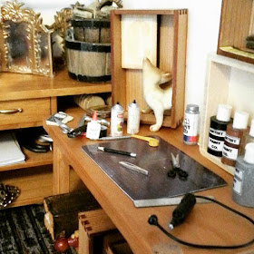 One-twelfth scale workbench top containing a cutting mat and various tools, including miniature tweezers, scissors and a dremmel.
