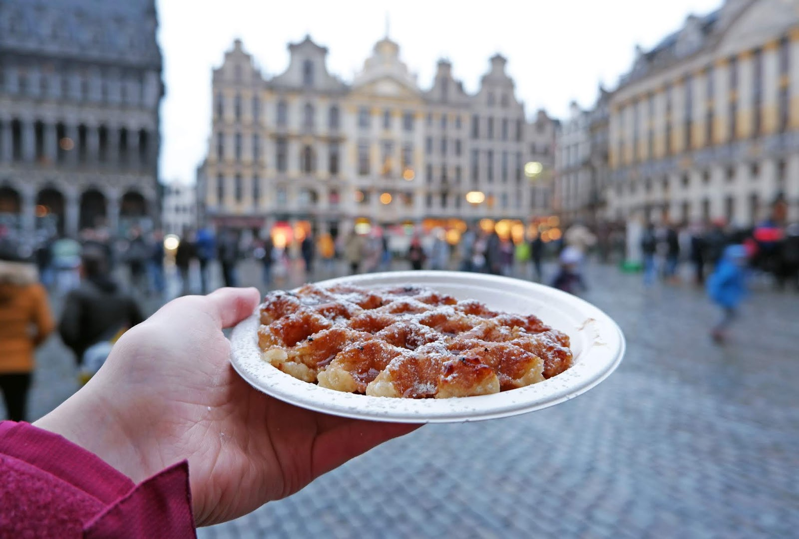 Eating a Liege waffle in the Grand Place, Brussels
