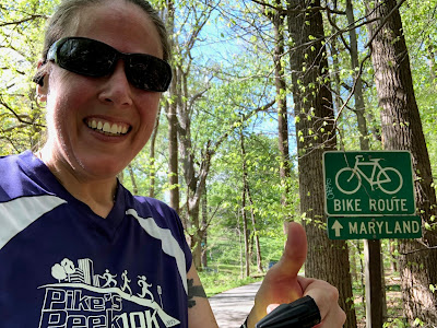 Photo of me giving a thumbs up next to a bike route sign indicating that Maryland is thatta way.