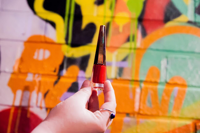 Holding Fenty Beauty's Stunna Lip Paint in front of a grafitti background