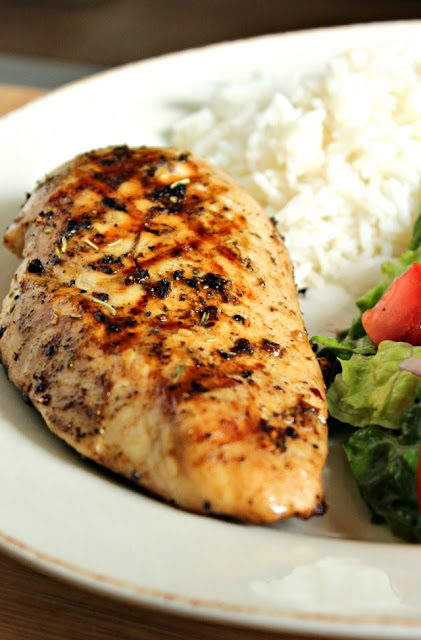 Barbecued Herb and Lemon Chicken breast with salad and rice on a plate.