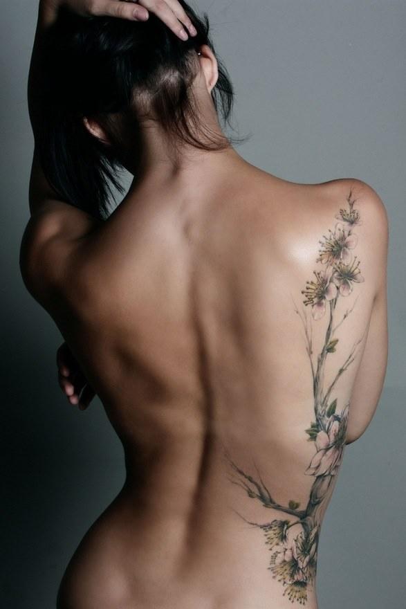 Una mujer de espaldas que lleva tatuado un arbol del cerezo