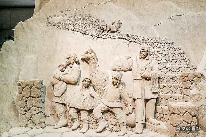 sculpture de sable famille et lama sur un escalier de pierre, dans les Andes