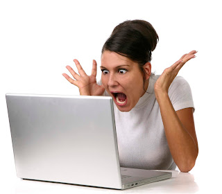 a woman with shocked expression staring at a laptop
