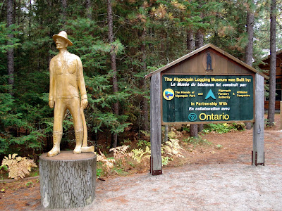 A wooden sculpture of a 19th century Ontarian logger stands at the entrance to the Algonquin Logging Museum trail.