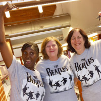 Three Olney staff members in grey shirts labelled the Beatles with images of the band members