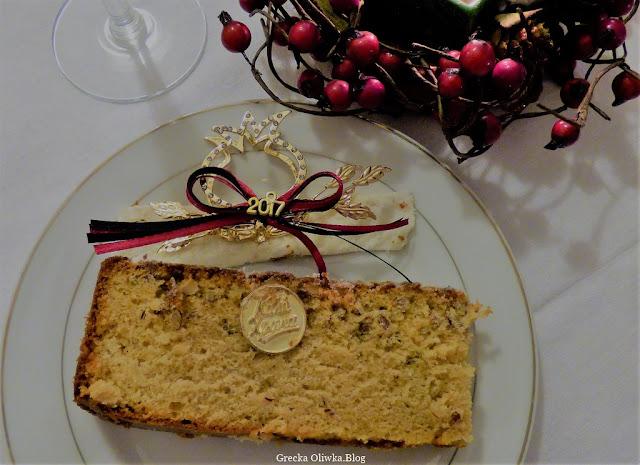 Na talerzu kawałek ciasta vasilopita obok w kształcie granatu talizman  na rok 2017 oraz czerwony stroik.