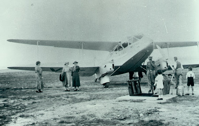A De Havilland Dragon Rapide of Holymans Airways on the ground in Canberra, 1935. Iris Taylor (George's fiance at the time) is second from the left.