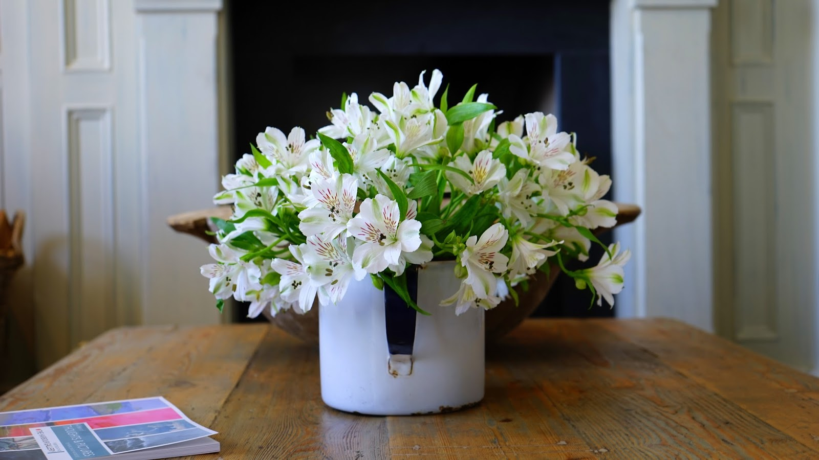 Spring flowers in a white pot on a wooden table