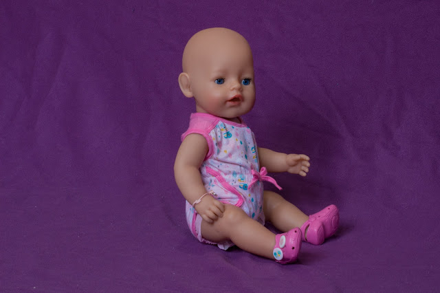 BABY born doll wearing one of the clothing sets which can be bought. The pyjamas are short sleeved all in one with cut of legs and the plastic shoes are like pink Crocs