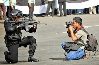 Policia encañonando a fotógrafo.