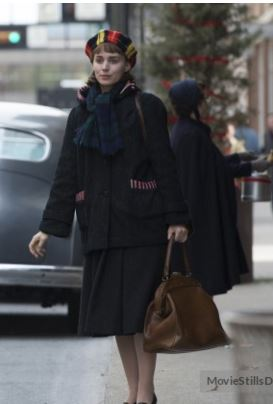 Rooney Mara andando na rua com casaco preto de frio e uma mala marrom na mão