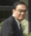 Snapshot from the chest up of a dark-haired middle-aged white man with eyeglasses, wearing a suit and tie, evidently turning to look at the camera as he walks past
