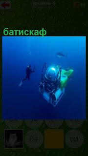 под водой двигается батискаф и аквалангист недалеко плавает