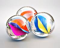 İçinde renkli dalgalı şekiller olan misket ya da cam bilyeler
