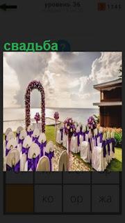 на поляне стоят стулья и арка, подготовка к свадьбе