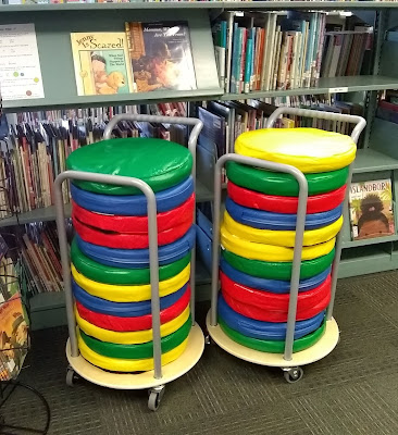 Two rolling storage containers with round base and metal side-braces in the front and back, each holding 12 circular cushions. The solid-colored cushions are in shades of green, blue, red, and yellow. Behind them are library shelves with children's picture books on them.