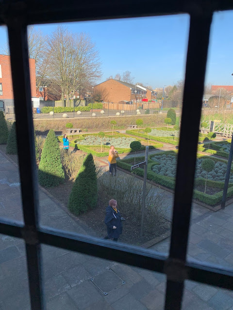 view to one of the garden areas outside Ordsall Hall, Salford with modern estate around.