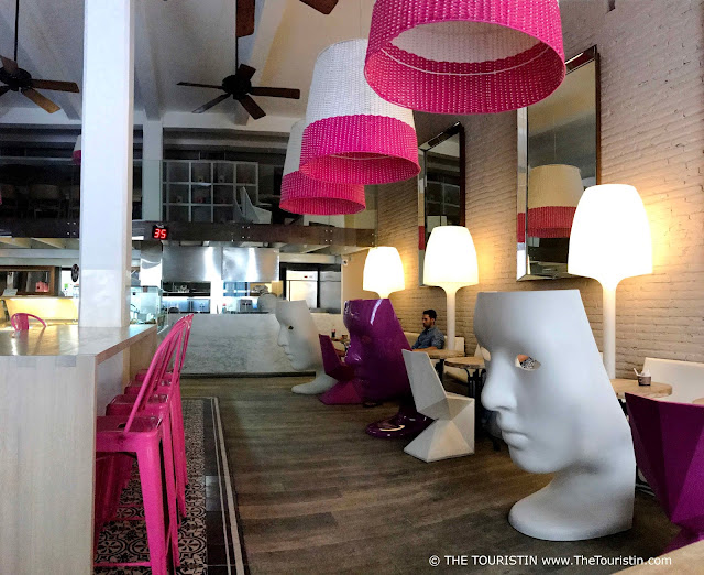 A cafe with a wooden floor pink and white chairs whereas some are sculpted in the form of a face.