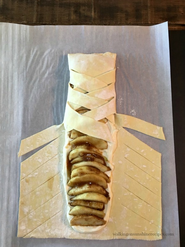 Start criss-crossing the sections of puff pastry to form a braid for the Apple Braid Recipe from Walking on Sunshine Recipes