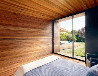 Tavanı, tabanı ve duvarları lambri kaplanmış modern bir konteyner evdeki büyük pencereli yatak odası