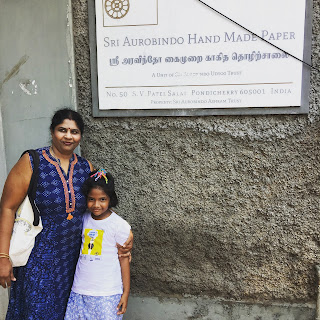 Family posing outside the gate to the Sri Aurobindo Paper Factory in Pondicherry