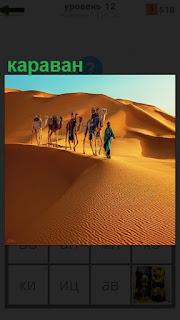 В пустыне по песку двигается караван на верблюдах и люди